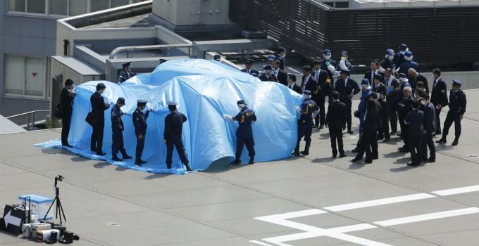 Poliziotti e funzionari della sicurezza intorno ad un telone che copre un drone radioattivo sul tetto della residenza ufficiale del Primo Ministro Shinzo Abe a Tokyo il 22 aprile 2015.