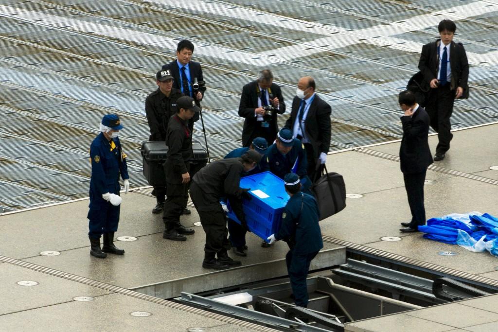 Funzionari e poliziotti trasportano il drone per farlo analizzare